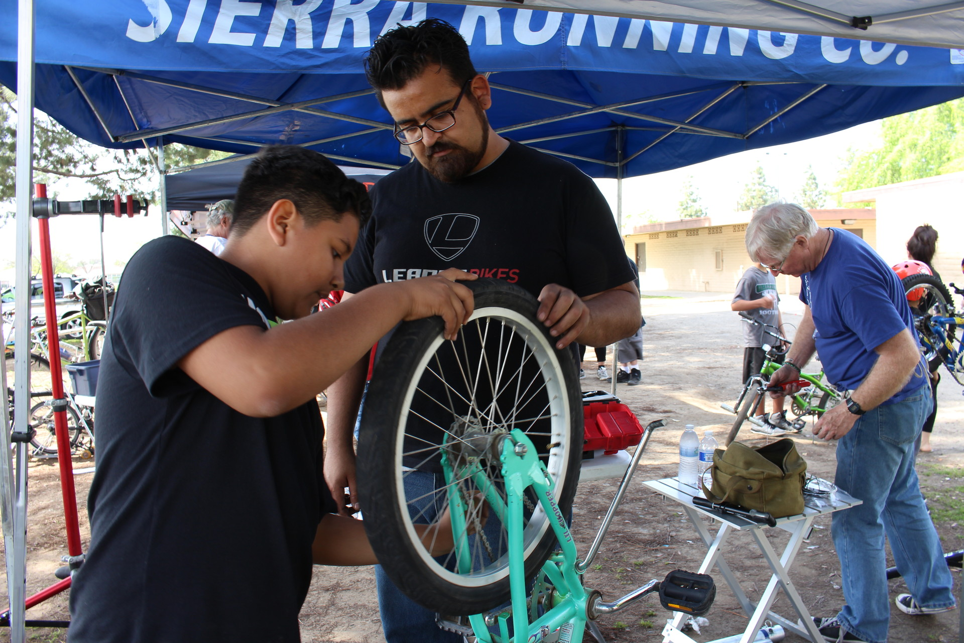 Jaime Rangel, 26, helps Gustavo Ruiz, 12, fix the flat tire on his bike at the Mosqueda Community Center park. Rangel says he makes a point of showing kids and adults who may not have funds to repair their bikes at a shop, how to fix their bikes on their own.