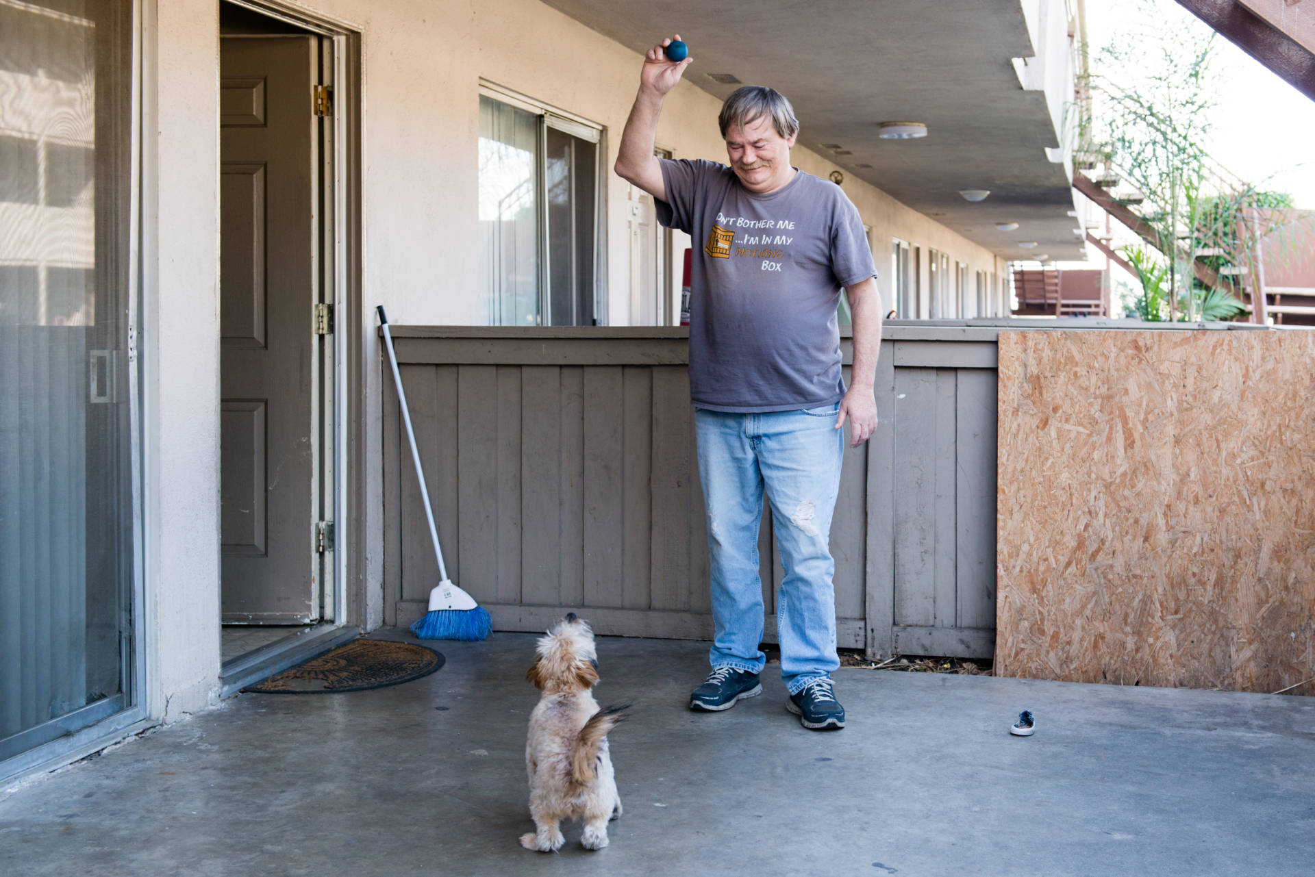 Donald Meade plays with his puppy, Scrappy, at his new apartment in Fullerton, Calif.