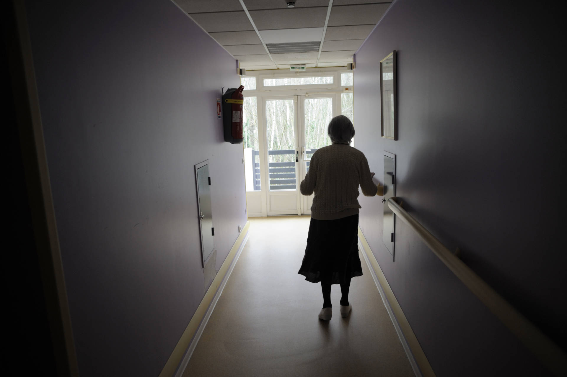 A woman, suffering from Alzheimer's disease, walks in a corridor in a retirement house.