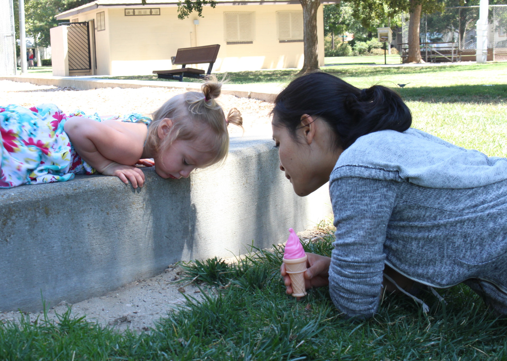 Stephanie Okada, an occupational therapist, and Isabella look for ants near a playground in the Sacramento area, as part of Isabella's weekly play and speech therapy session. Donita Escamilla, who became a foster parent for Isabella and recently adopted her, says therapy is helping the toddler develop her emotions and social skills.