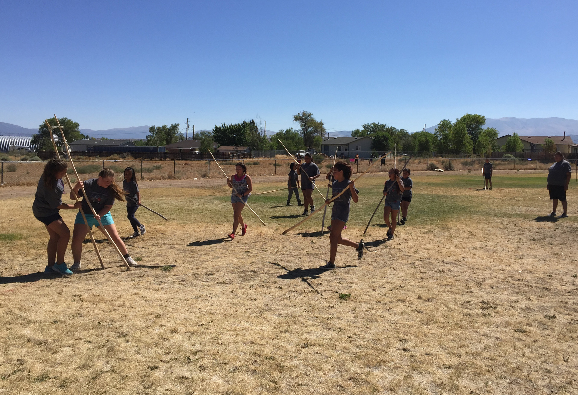 Young Washoe women play the game Sigayuk. They battle for control of a short rope with their aspen tree trunks, hoping to score a goal.