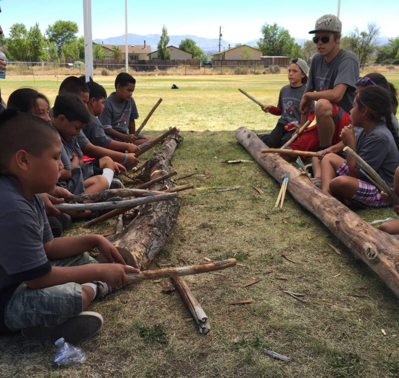 Herman Fillmore (upper right) teaches young Washoe kids how to play the game Hinoyowgi in Gardnerville, Nevada. This game incorporates rhythm and song.