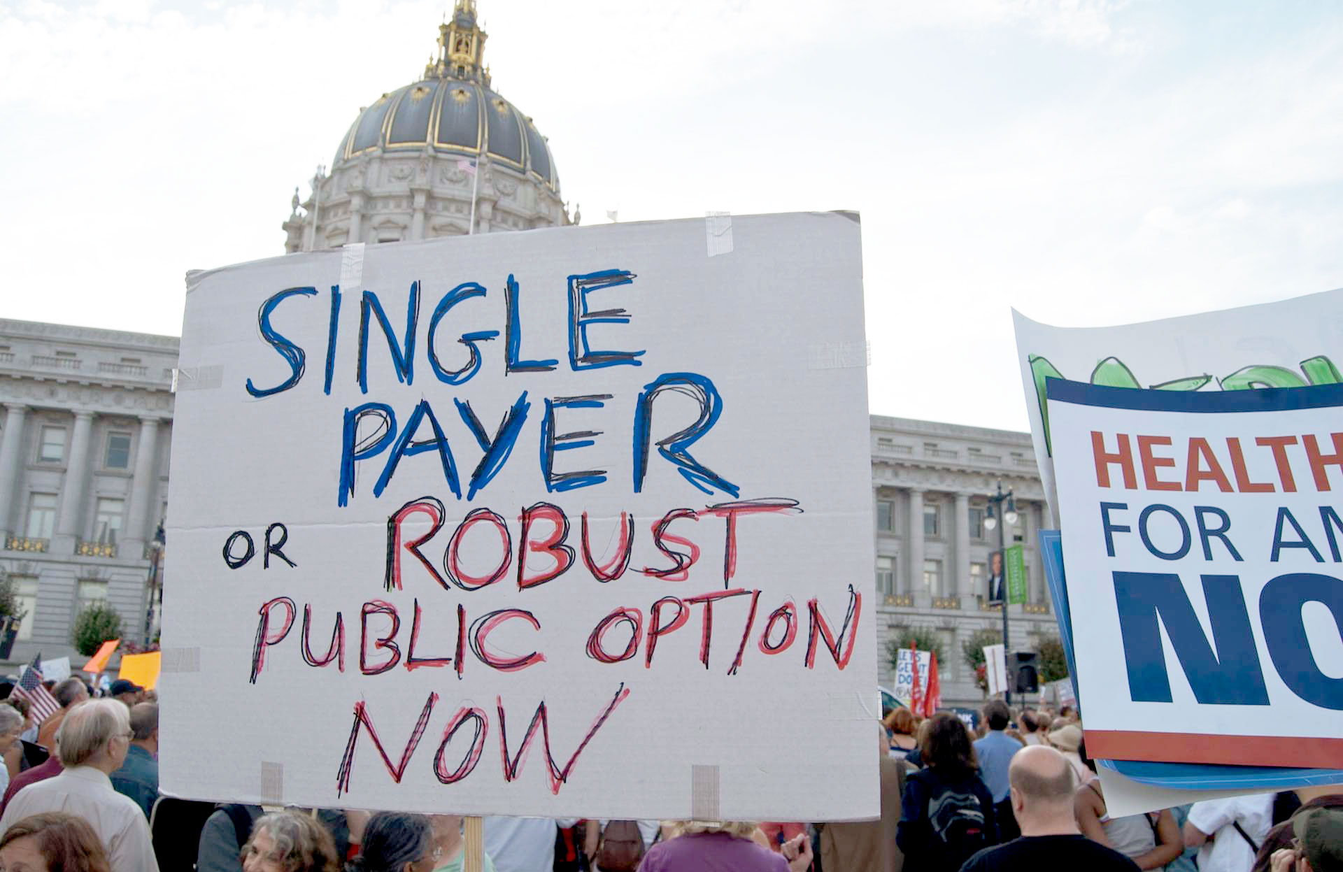 A demonstrator holds a sign at a health care reform rally at San Francisco City Hall.