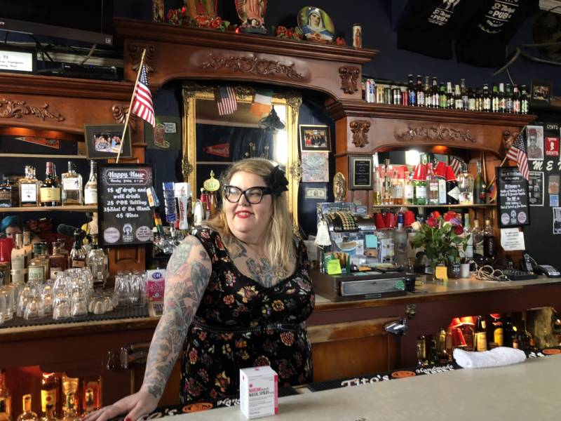 Amy Rothbauer, a bartender at St. Marys Pub, poses with the box of Narcan that she keeps behind the bar, next to the first aid kit.