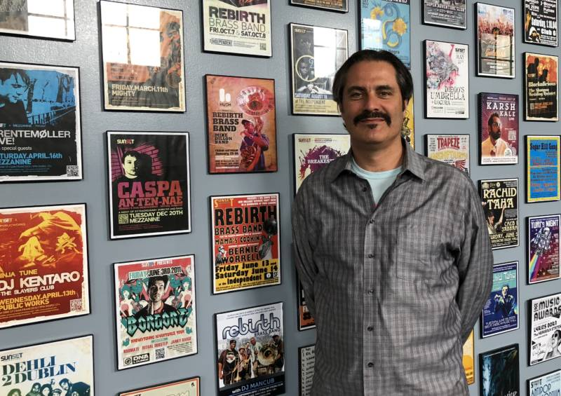 Robbie Kowal, creative director of HUSH Concerts in San Francisco, stands in front of a wall of concerts his company's produced.