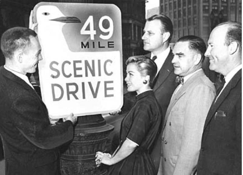 Designer Rex May shows off the original 49 Mile Scenic Drive sign.