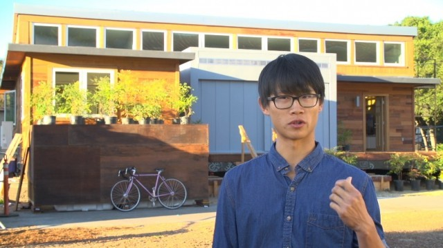 Stanford student Derek Ouyang gets ready to lead a tour of his team's solar house. (Joshua Cassidy/KQED)