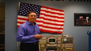 Silicon Valley venture capitalist Steve Jurvetson stands next to some of his space memorabilia, including a prototype of the American flag planted on the moon. Image by Arwen Curry / KQED Science.