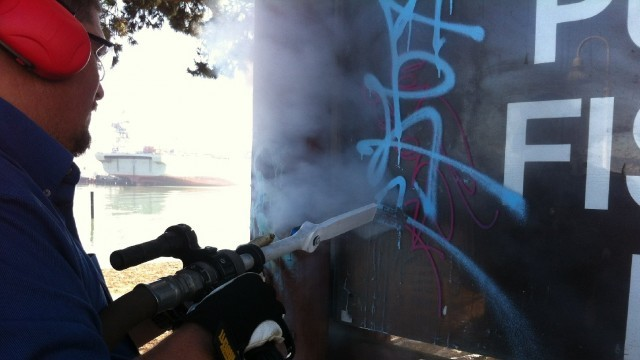 Dennis Barfuss, a specialist in dry ice-blasting, demonstrates removing graffiti at Agua Vista Park in San Francisco. (Photos by Lindsey Hoshaw/KQED)
