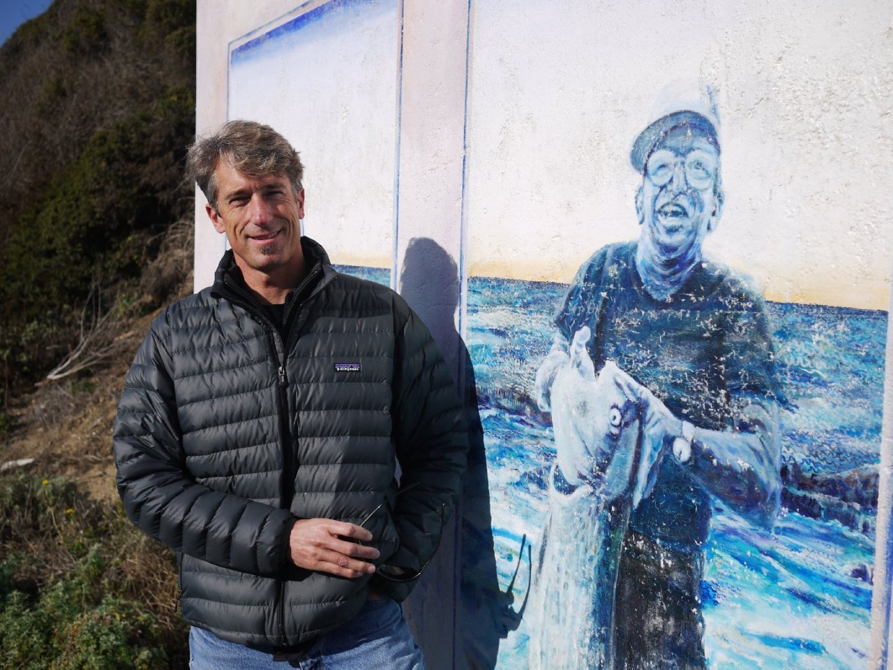 Mike Wallace used to bring his high school surf team to practice at Martins Beach. Here, he stands next to a mural depicting the beach's former owners. (Amy Standen/KQED)
