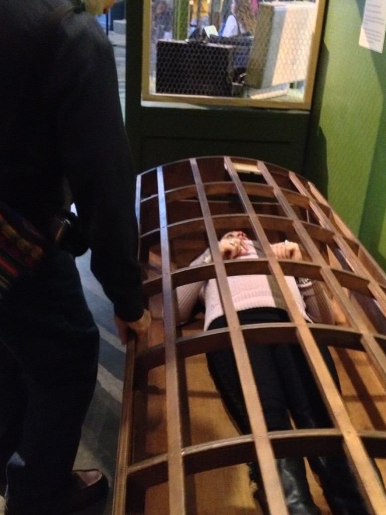 An Exploratorium visitor tries out the 19th-century Utica Crib, designed to prevent patients from harming themselves or others. (Photo: Liza Gross)