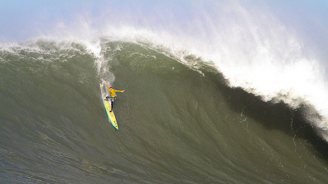 A surfer drops into a wave at Mavericks in 2010. (rickbucich/Flickr)