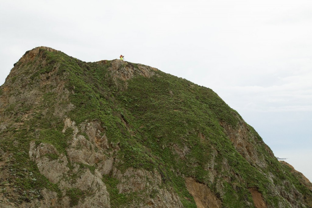 A researcher monitors nesting shorebirds from a peak above the new Devil's Slide Trail. (Josh Cassidy/KQED)