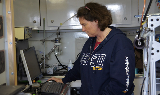 Kim Prather watches are air particles are tested, inside a research trailer in Bodega Bay. (Lauren Sommer/KQED)