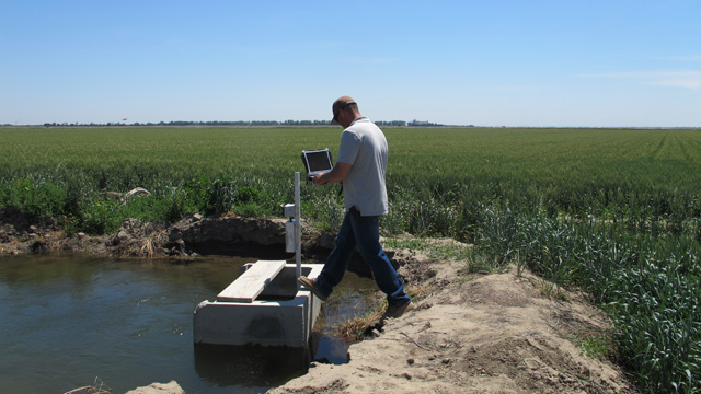 Chad Navarrot, operations manager for Reclamation District 108, demonstrates measuring water sent to a field.