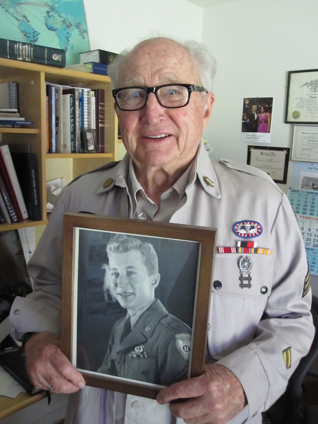 Don Foster poses with a photo of himself from World War II. (Scott Shafer/KQED)