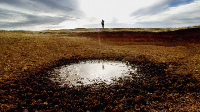 Farmer John Magill ponders a dried-up reservoir on his farm in Parkes, in 2006. (Ian Waldie/Getty Images)