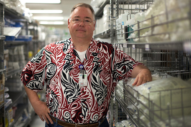 Reid Kennedy, materials manager at San Francisco General Hospital, stands next to racks of saline solution. (Mark Andrew Boyer/KQED)