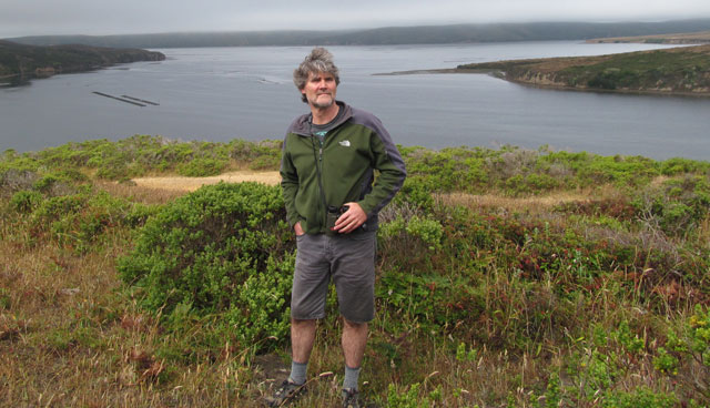 College of Marin biology professor Joe Mueller on a ridge overlooking Home Bay, part of Drake's Estero. The oyster farms are visible in Home Bay. (Cy Musiker/KQED)