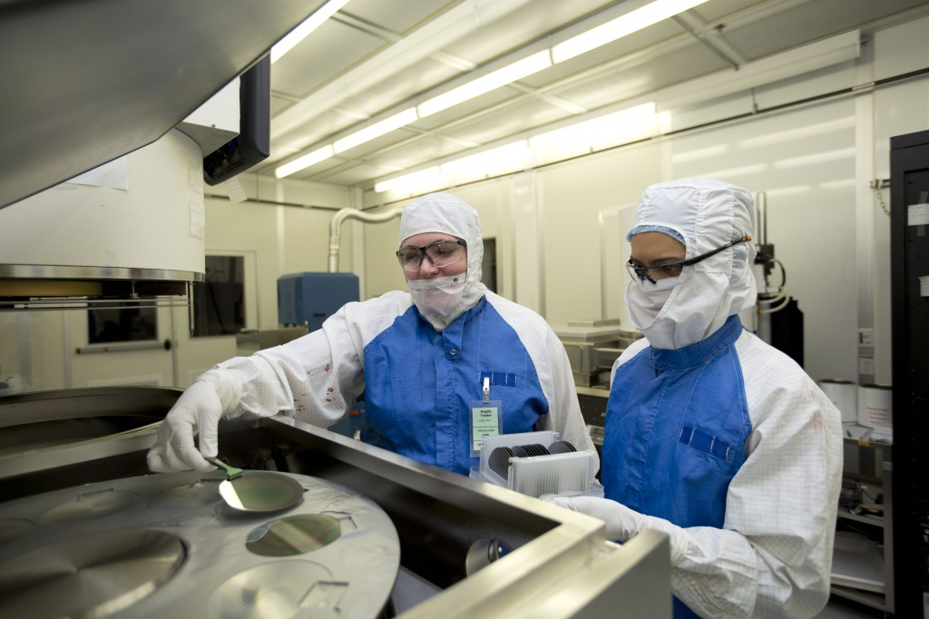 Lawrence Livermore engineers Angela Tooker and Vanessa Tolosa load silicon wafers into a metal deposition chamber during the development of the neural device. (Courtesy of LLNL)