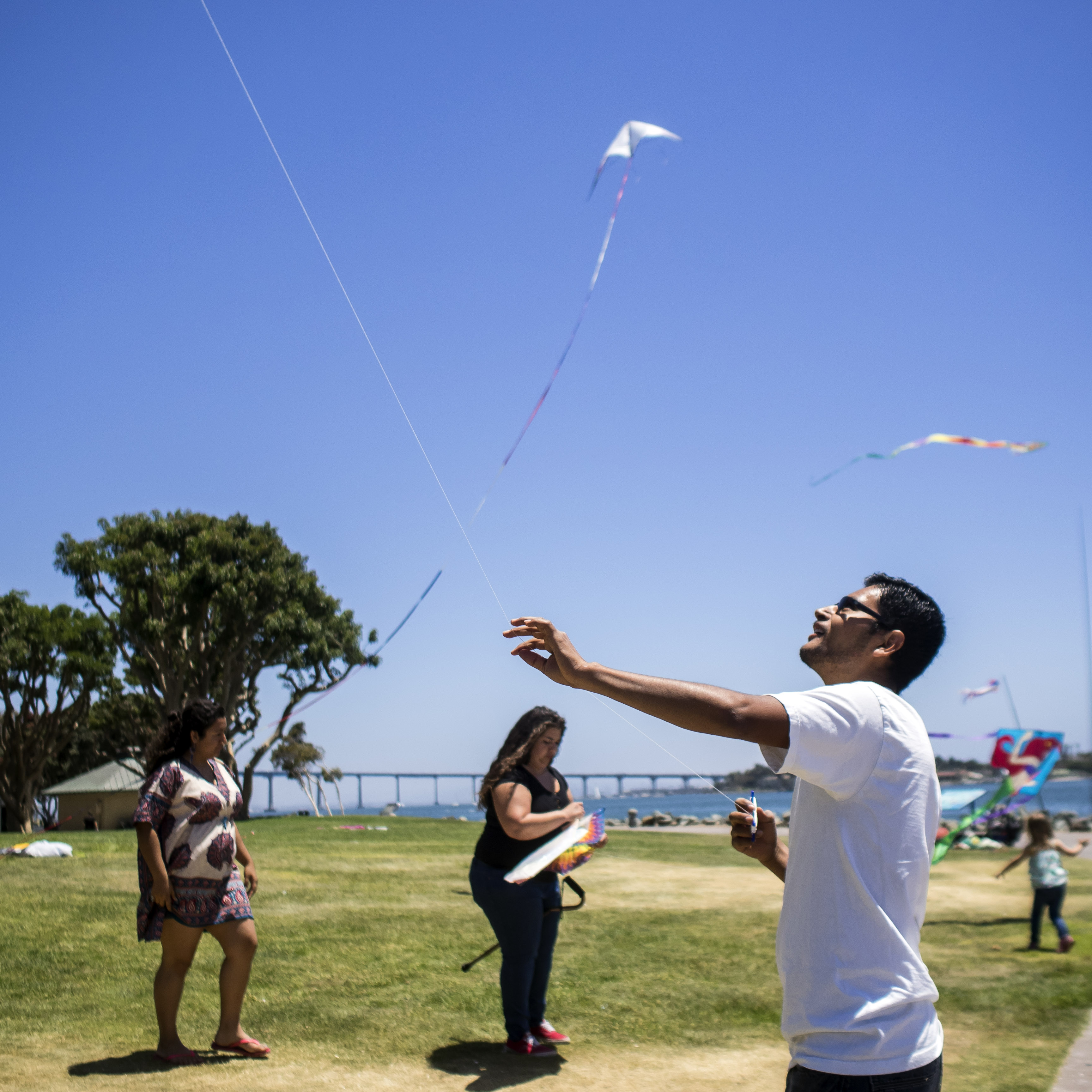 Young people taking part in a mental illness prevention program called Kickstart fly kites at San Diego's Seaport Village. Marvi/KQED)