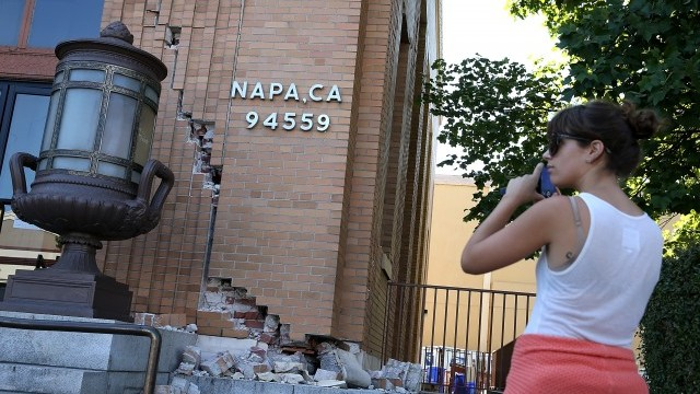 A passerby stops to take a picture of damage to the Napa post office. (Justin Sullivan/Getty Images)