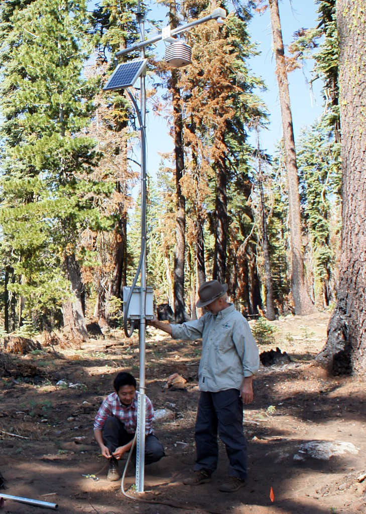 UC Merced's Roger Bales and Ziran Zhang work on a snow sensor tower in the Tahoe National Forest. (Lauren Sommer/KQED)