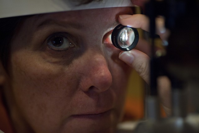 Dr. Linda Olmos De Koo examines Lisa Kulik's prosthetic retina at the USC Eye Institute. The device helps Kulik differentiate between light and shadows so that she can better interpret the world around her. Benjamin Brayfield/KPCC)