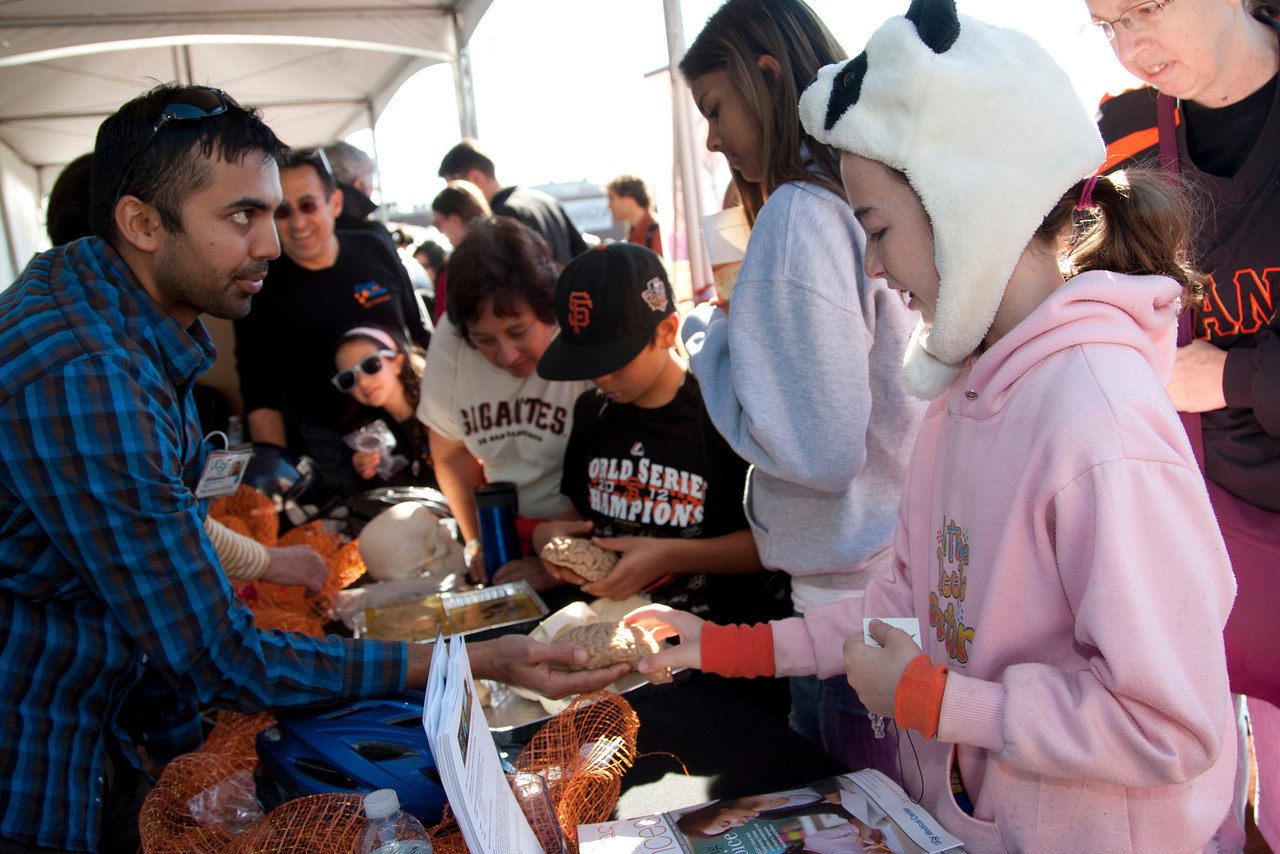 Dr. Mitul Kapadia, left, speaks with Talia Haber, 10, about brain injury prevention at one of the UCSF booths at the Bay Area Science Festival held at AT&T Park in 2012. Photo by Cindy Chew