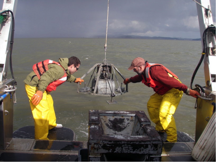 "Jeff Hansen and Daniel Hoover send a ""sand grab"" into San Pablo Bay to collect sand samples. (Amy Foxgrover/USGS)"