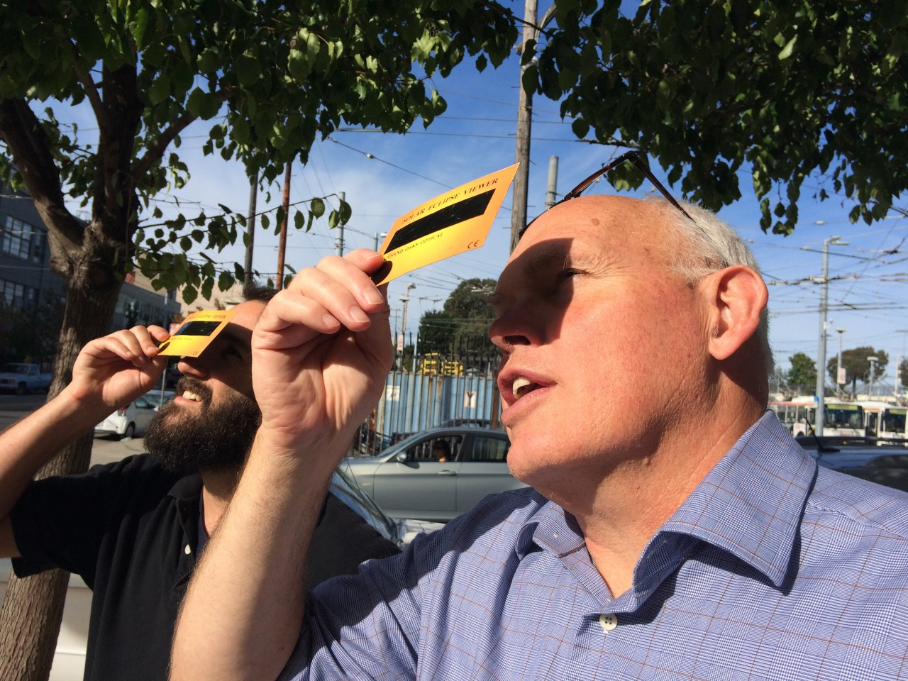 Adam Grossberg and Dan Brekke of KQED step outside to see the eclipse. (Olivia Hubert-Allen/KQED)