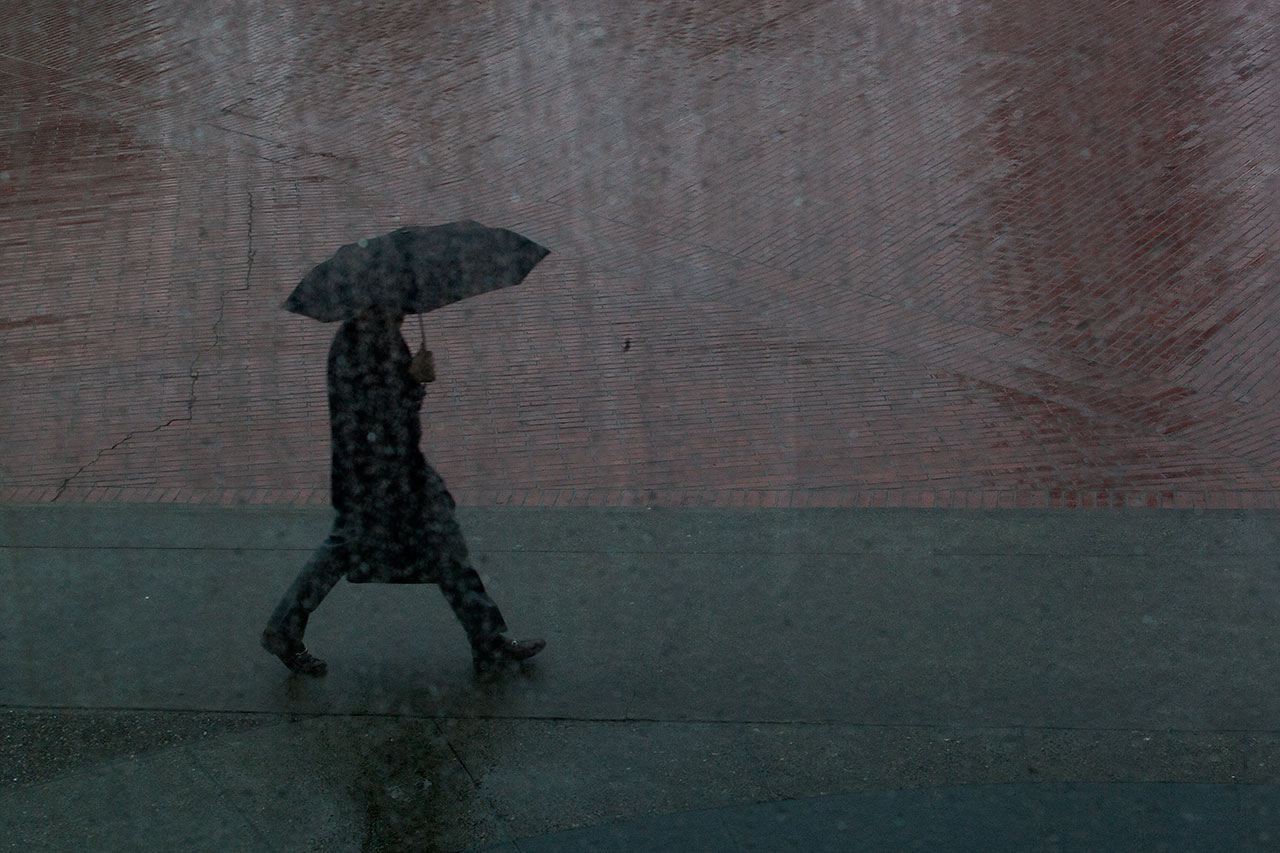 A pedestrian with an umbrella walks in the rain in front of San Francsico's Embarcadero Center. (Mark Andrew Boyer / KQED)