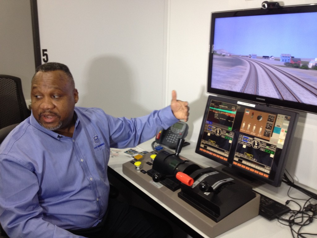 Using a simulator, Union Pacific's William Boyd demonstrates technology making sure train operators don't go too fast or end up on the wrong track. (Daniel Potter/KQED)
