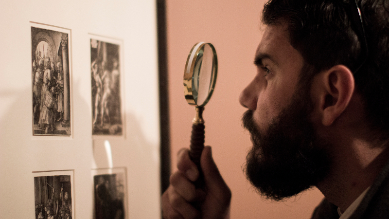 Man with magnifying glass and print
