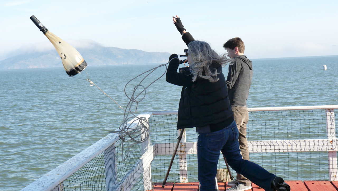 Melissa Dubose of the Romberg Tiburon Center casts her plankton net, with producer Josh Cassidy looking on (Mallory Pickett/KQED)