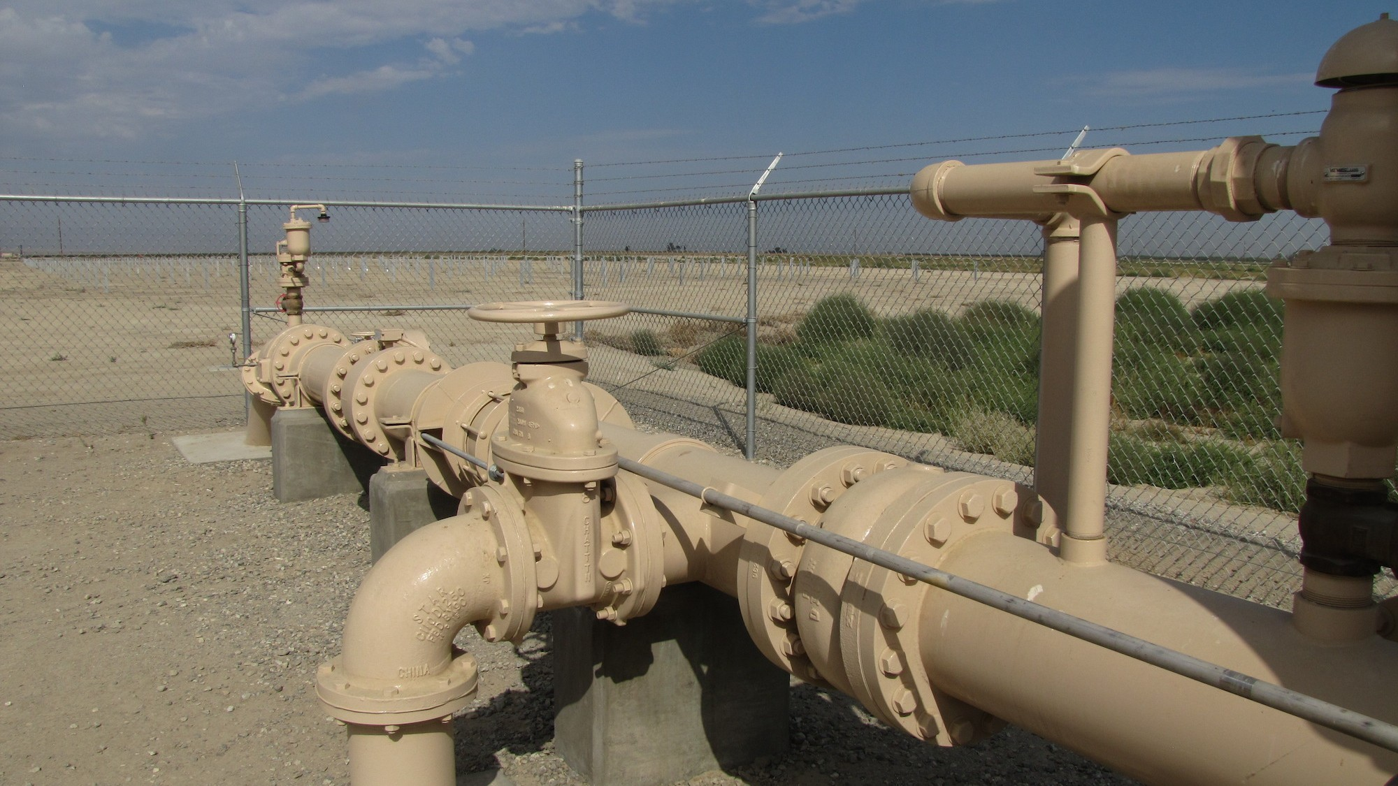 A security fence guards groundwater pumps in the San Joaquin Valley. (Craig Miller/KQED)
