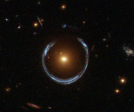A gravitational lens of a much greater scale: a giant elliptical galaxy focusing the light of a more distant galaxy into a ring shape.  (HST/NASA)