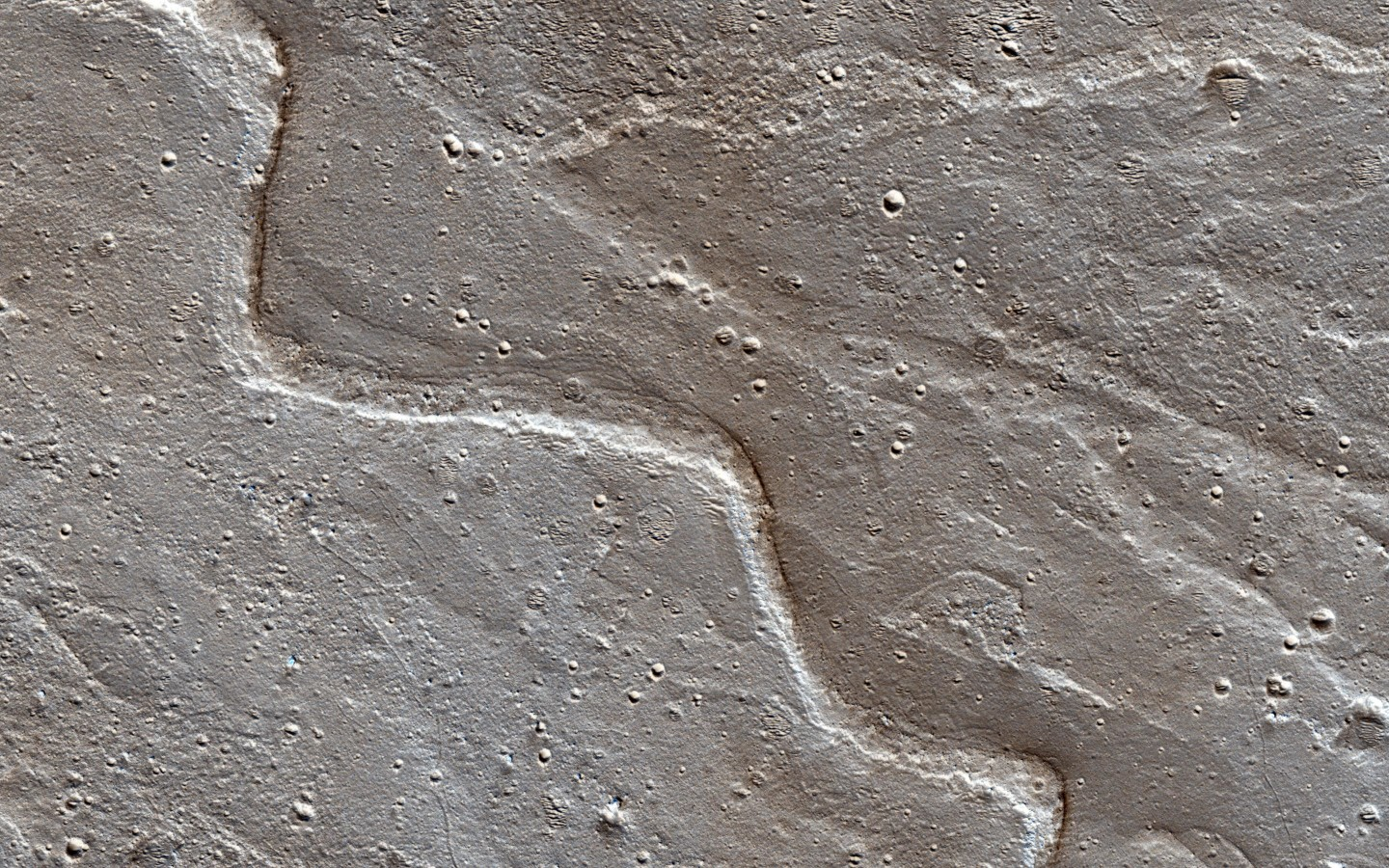 The sinuous ridges on the Orson Welles bajada mark the paths water took as it flowed into this crater. The sinuosity of the ridges tells us something about the speed of the water flow. Fast-moving flows tend to be straighter than slow-moving. (NASA/JPL-Caltech/Univ. of Arizona)