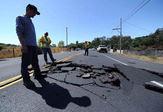Nicholas George looks under a buckled highway just outside of Napa, California after a 6.1 Earthquake struck the area on August 24, 2014. More than 80 people were injured after the quake caused fires, significant structure damage, water main breaks, and power outages throughout the region.