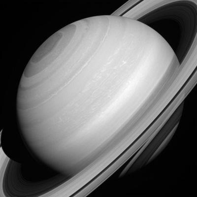 Saturn's seemingly serene cloud-tops, polar vortex, and translucent rings.