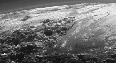 Pluto's ice mountains casting sunset shadows across the cold landscape.