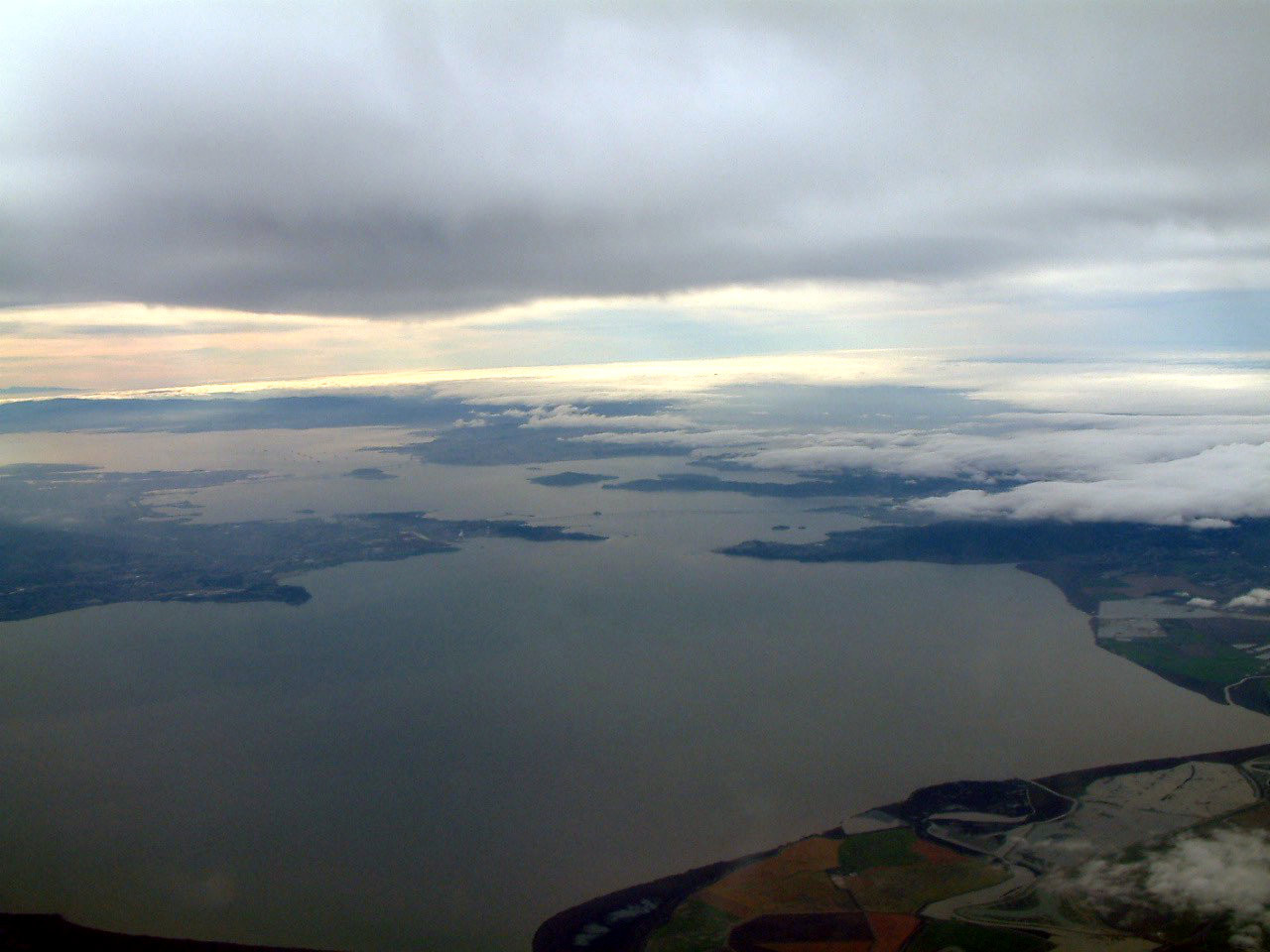 A view out the window of the NOAA research plane, with the Richmond-San Rafael Bridge in the distance. The plane is gaining altitude to fly into the storm cloud.