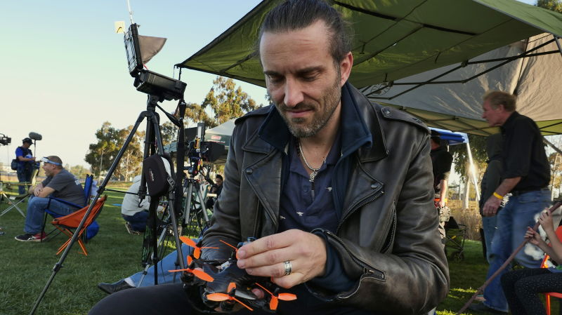 A drone racing pilot adjusts his drone before the start of a race.