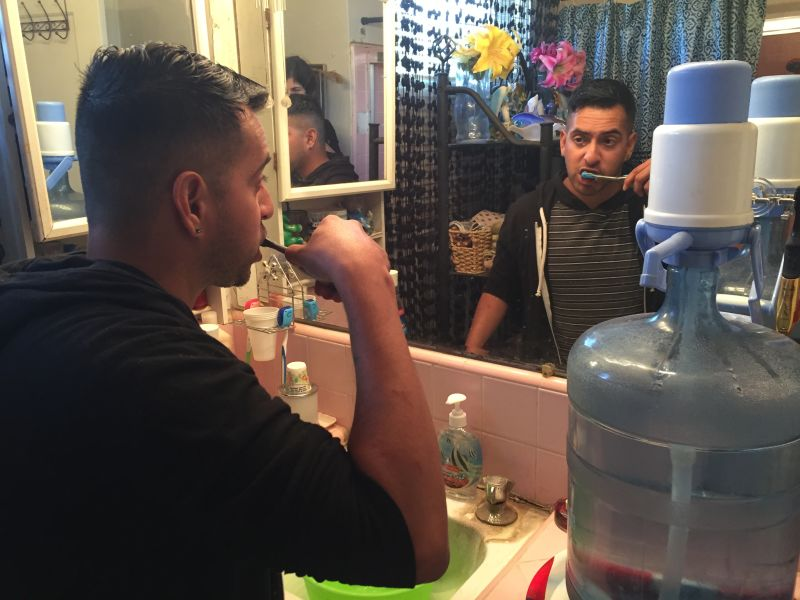 Guillermo Lopez brushes his teeth using a portable water jug. He and his mother lived without running water for nine months after their well went dry in rural Fresno County.