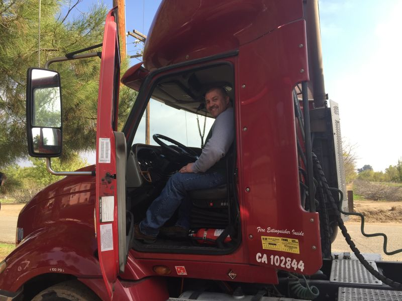 Trucker Shannon Doyle with his big rig. Every day, he drives 500 miles from Fresno to Los Angeles, hauling auto parts.