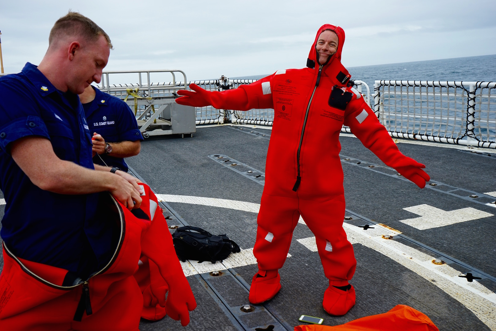 "A crew member tries on a cold-water survival suit, known as a ""Gumby suit."""