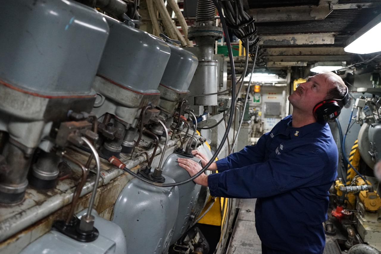 "Master Chief Tom Stone inspects one of the ship's three service diesel generators, which provide ""hotel"" services like light and ventilation, as opposed to the six propulsion generators."