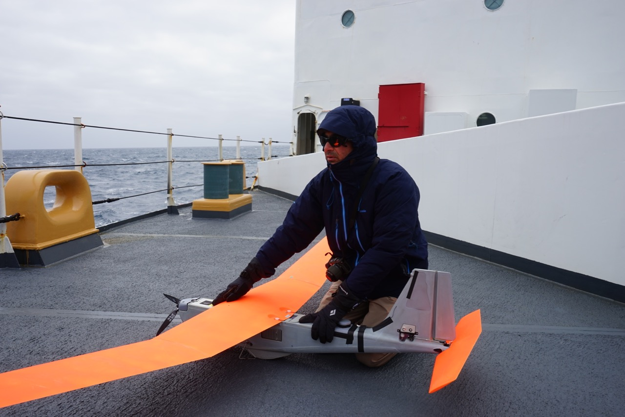 Todd Jacobs of NOAA holds the Puma down against high winds.