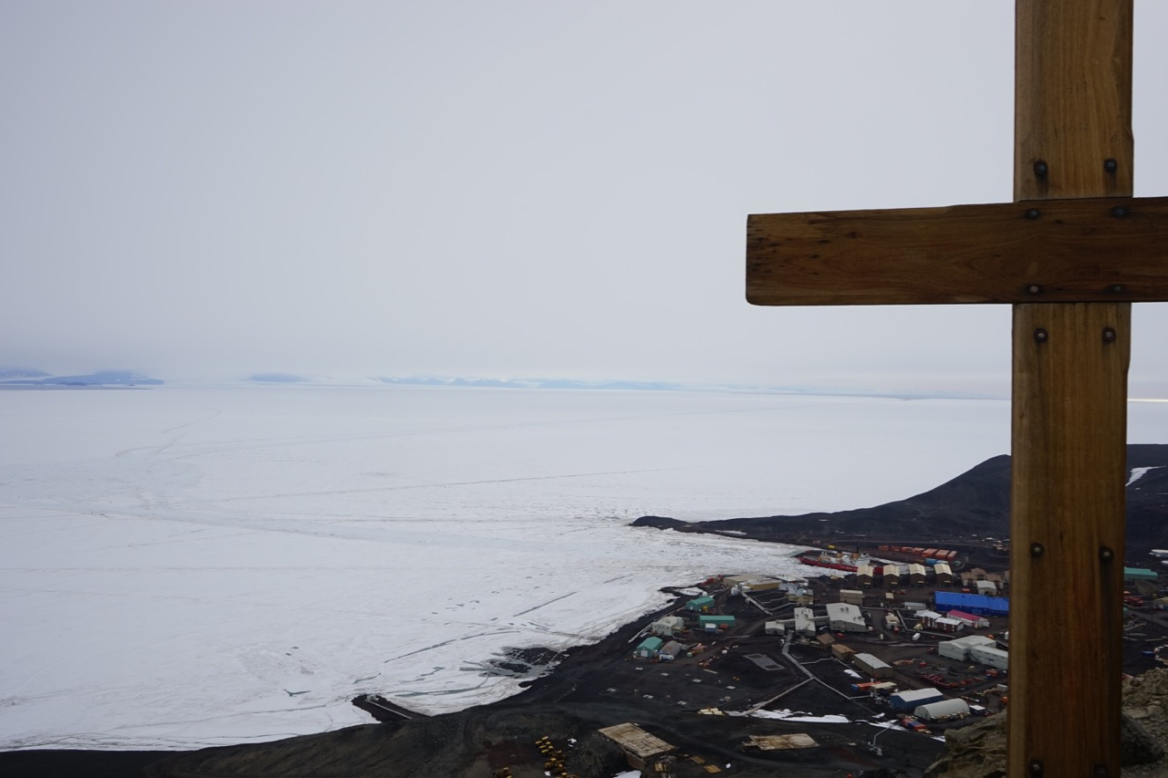 View of McMurdo Station from Observation Hill, where a cross has been erected to the Robert Falcon Scott expedition, whose members died on their return from the South Pole. Polar Star is docked. Note the turning basin at left and the channel, dimly visible, which runs out to open water in the distance.