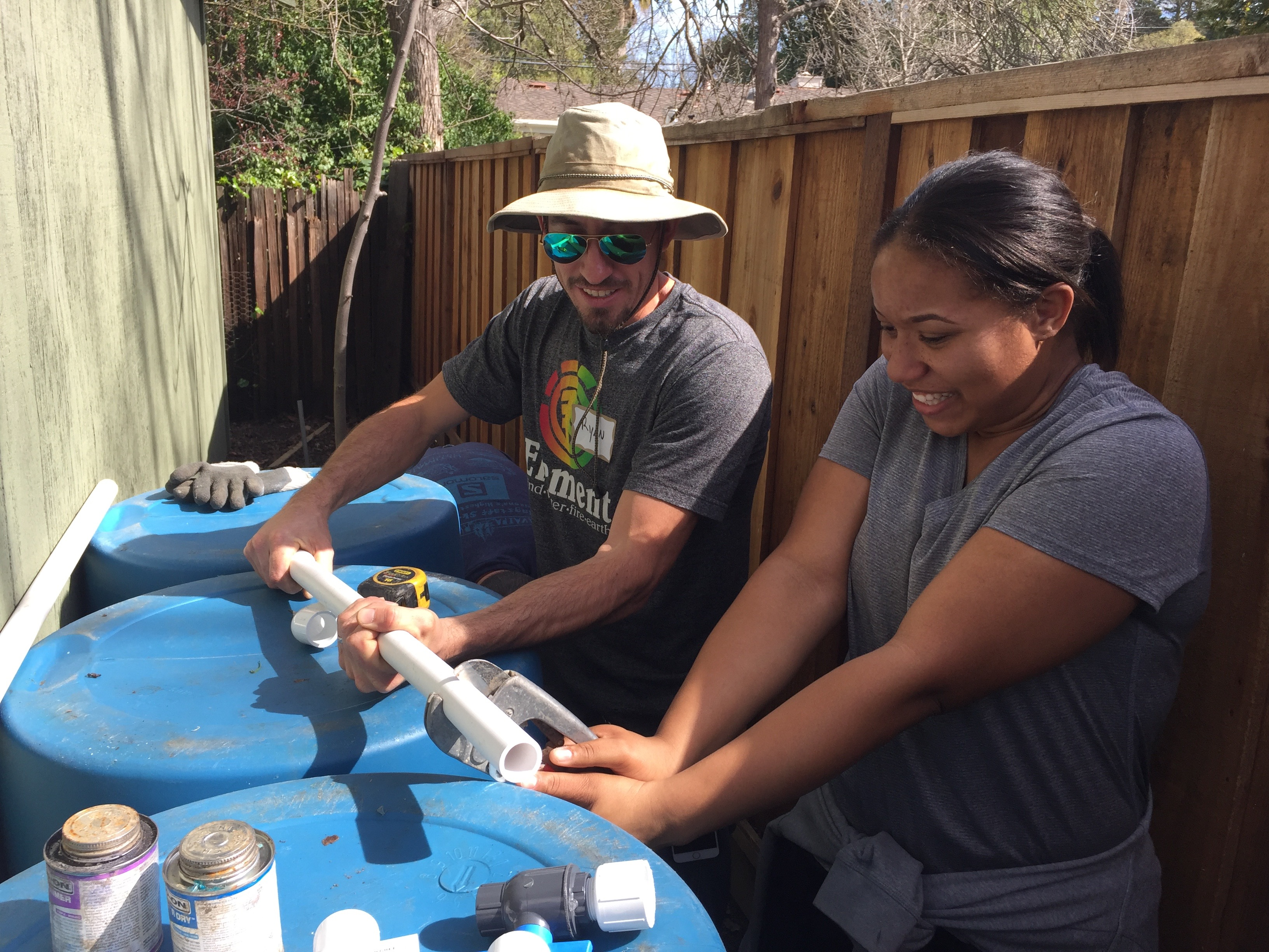 Landscape designer Ryan Kelsey shows Zakeisha Plummer how to cut PVC piping for a backyard rainwater capture system in Walnut Creek.